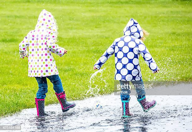 Two Young Girls Splashing Through Puddle in the Rain