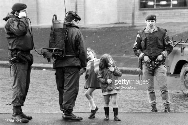 Two young girls stand with members of the British Army's Parachute Regiment, one of whom speaks on a field telephone, in the primarily Catholic,...