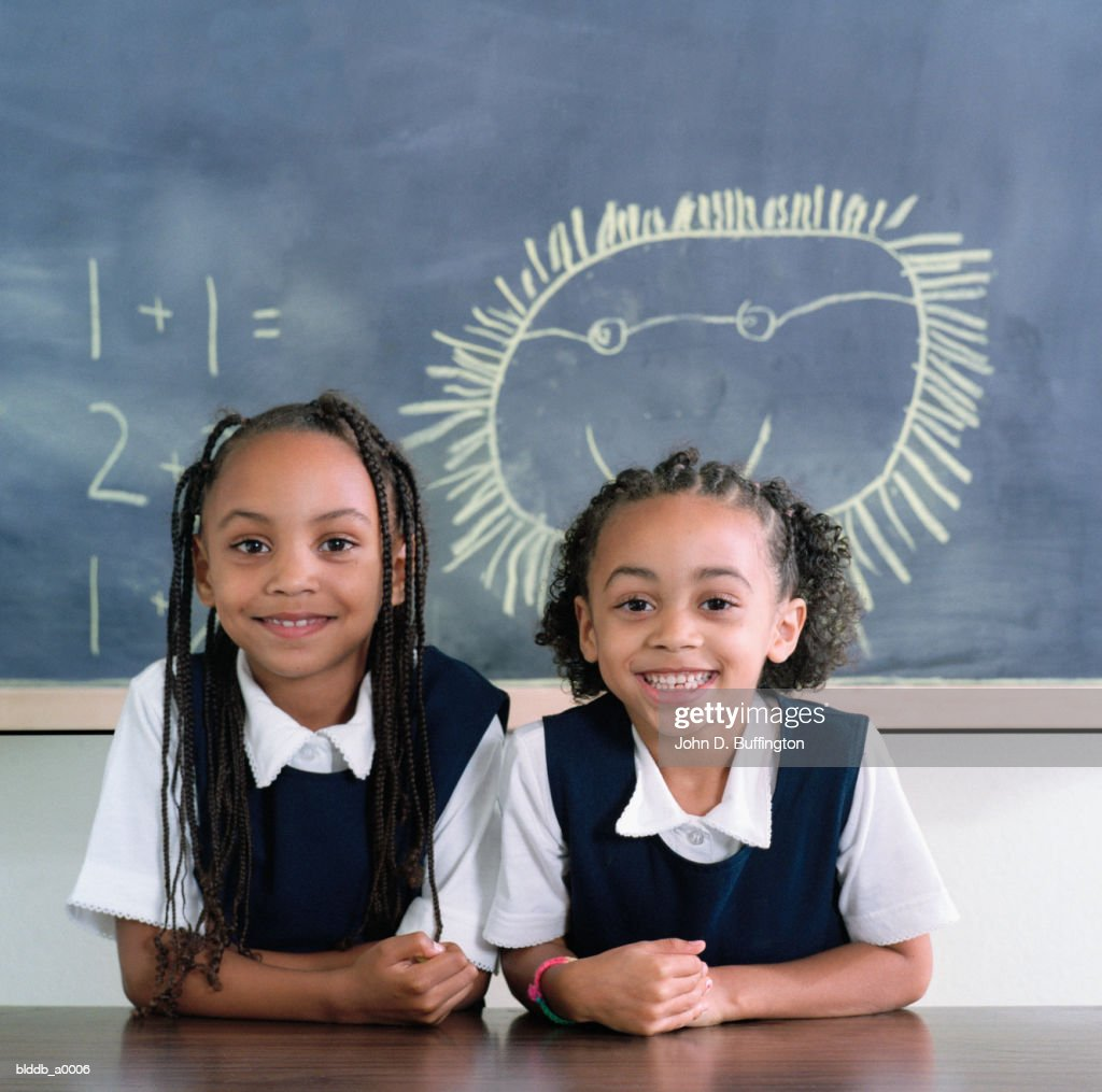 two young girls standing and smiling in front of a blackboard in a