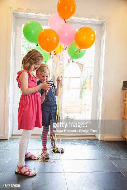 Two Young Girls Standing Inside A House With Balloons While Looking At Pictures On A Camera
