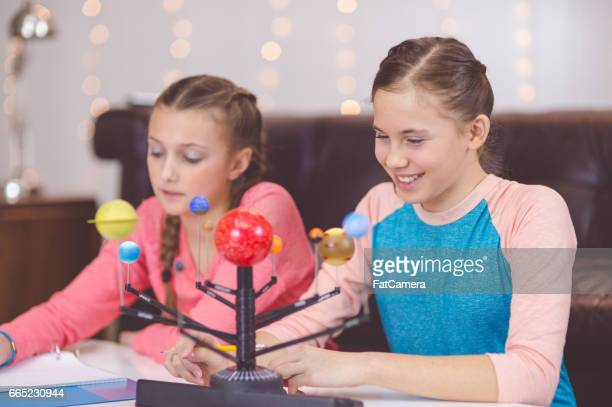 Two young girls studying the solar system