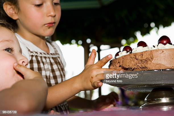 two young girls tasting cream cake