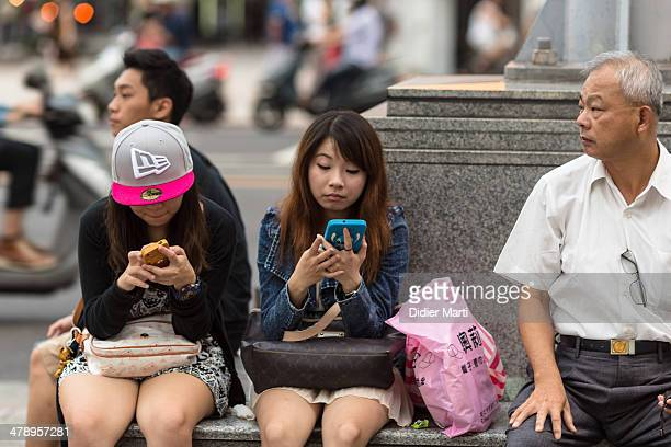Two young girls using their smartphone while an older man looks around in taipei Taiwan