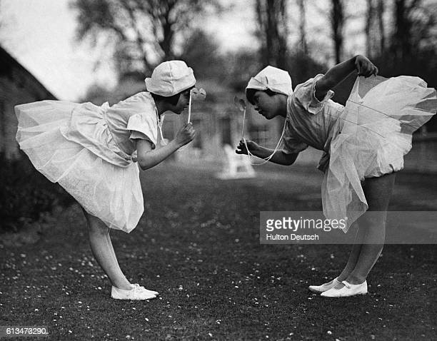 Two young girls view each other through lorgnettes as they bow during a May Day dance performance at the Stoke Park Colony school | Location...