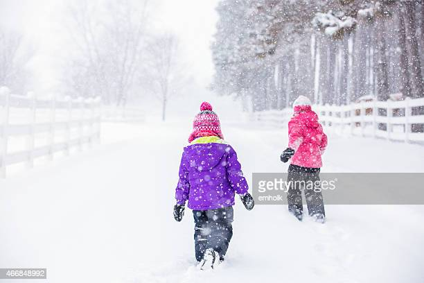 Two Young Girls Walking in Winter Snow Storm