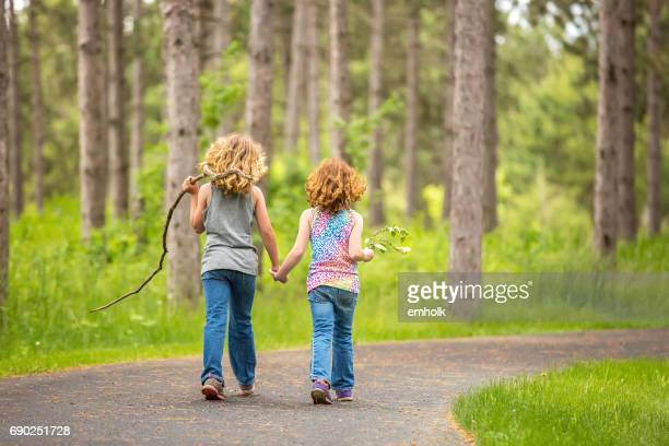 two young girls walking through woods on paved path - lane sisters stock photos and pictures