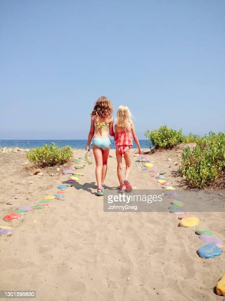 夏休みに一緒にビーチに歩いている二人の若い女の子 - モバイル撮影 ストックフォトと画像