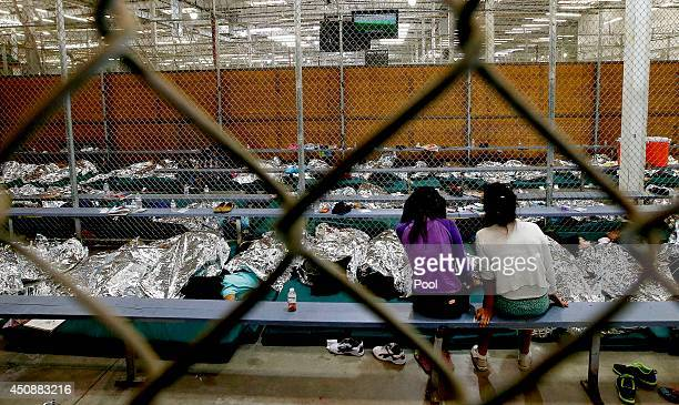Two young girls watch a World Cup soccer match on a television from their holding area where hundreds of mostly Central American immigrant children...