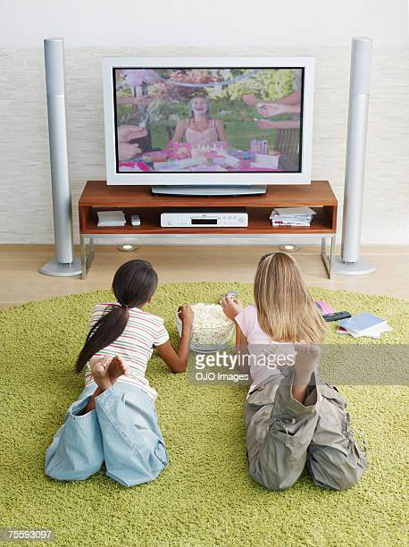 Two young girls watching television eating popcorn