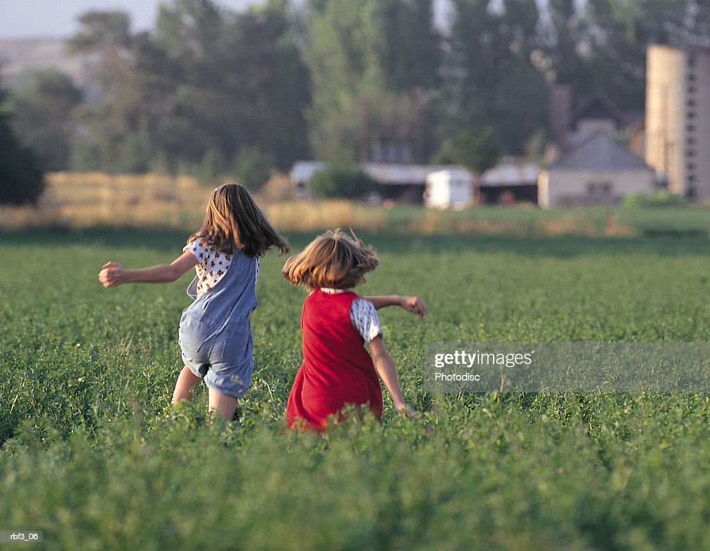 two young girls wearing red and blue jumpers walk through a green field toward a farm : Stockfoto