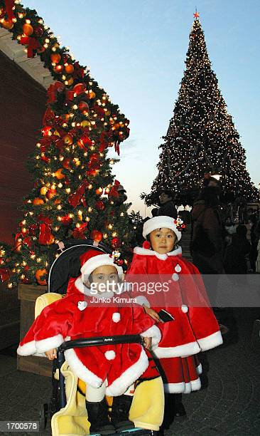 Two young girls wearing Santa Claus costumes stand in front of a large Christmas tree at the Tokyo Disney Resort on December 24 2002 in Tokyo