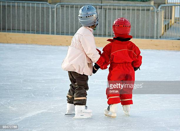 Two young girls with protective helmets skating.
