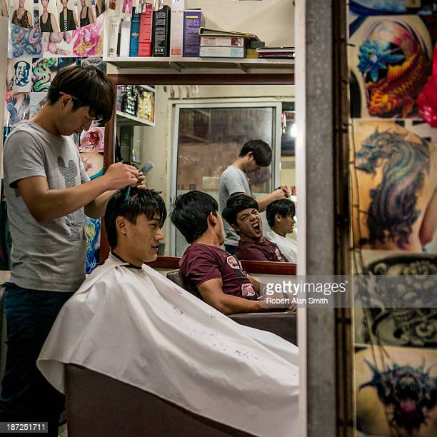Two young guys having a hair cut in a very small local barber/tattoo salon located in one of the small lanes in Shanghai