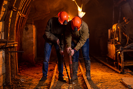 Two young guys in a working uniform and protective helmets, carry out work in the mine. Miners 1140430885