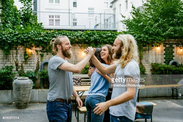 two young guys pleased to see each other at barbecue meetup with friends - greeting stock-fotos und bilder