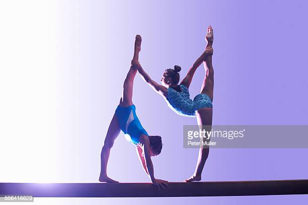 Two young gymnasts performing on balance beam