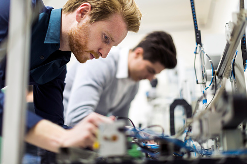 Two young handsome engineers working on electronics components 483784268