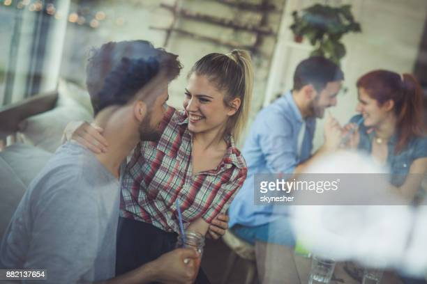 Two young happy couples sitting in a cafe and talking.