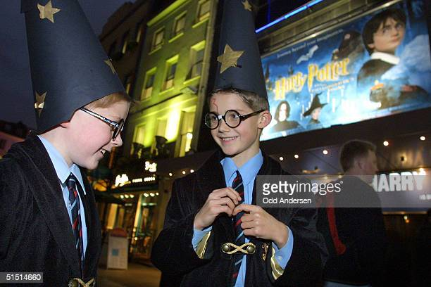 Two young Harry Potter fans dressed as their hero queue up outside the Odeon cinema at Leicester square in central London 16 November 2001 Thousands...