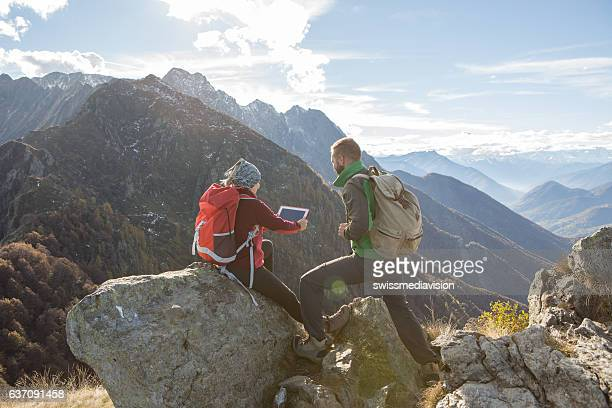 Two young hikers looking at digital tablet