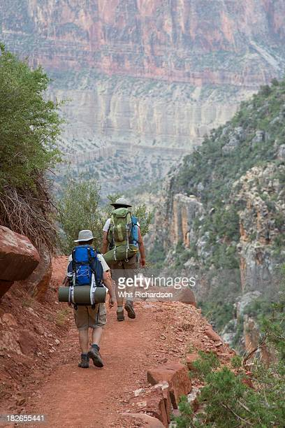 Two young hikers with backpacks hiking on a trail.