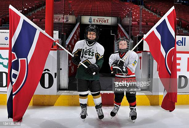 Two young hockey players hold the Montreal Canadiens team flag before the NHL game against the Pittsburgh Penguins on November 26 2011 at the Bell...