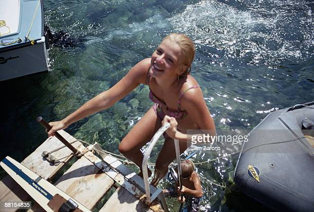 Two young holidaymakers climb onto a jetty after a swim August 1969