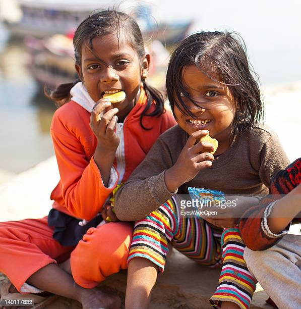5948700283 Two young indian girls eat biscuits at the Ganges river on February 1 2012  in the