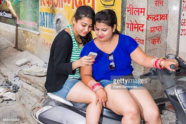 RISHIKESH UTTARAKHAND INDIA Two young indian women in shorts are sitting on a scooter and using a mobile phone