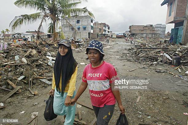 Two young Indonesian women walk among the debris in Meulaboh 08 January 2005 after the city was flattened by an earthquake and tsunami 26 December...