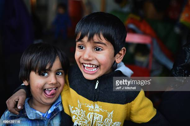 Two young Iraqi brothers pose for a photograph in the camp known as the 'New Jungle' on December 1 2015 in Calais France Thousands of migrants...