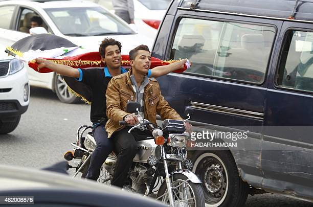 Two young Iraqi men riding a motorbike wave an Iraqi flag in Najaf on January 23 2015 to celebrate the victory of the Iraqi National Football team...