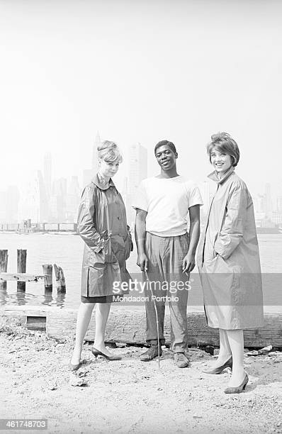 Two young Italian models wearing raincoats named Flora and Lucia are posing on the bank of the Hudson river together with a smiling black guy humbly...