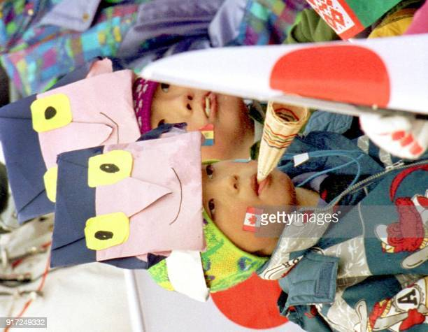 Two young Japanese children with flags painted on their faces and wearing folded paper models of the Olympic mascots the 'Snowlets' watch the women's...