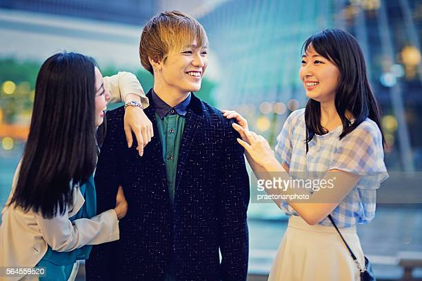Two young Japanese girls are joking with a guy