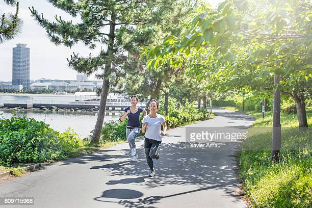 Two young Japanese women running in the park
