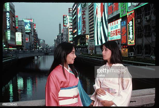 Two young Japanese women stand on Osaka's Dotonbori Bridge wearing traditional kimonos Bright neon signs light the city behind them