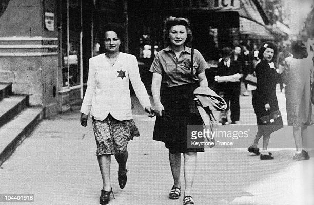 Two young Jewish girls wearing the yellow star in a street of Paris Wearing of the star was made compulsory by French law starting on May 29 1942