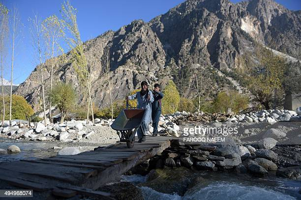 Two young Kalash cross a stream in Bumburate valley on October 30 2015 Kalash considered the only surviving animist tribe of Pakistan was badly...