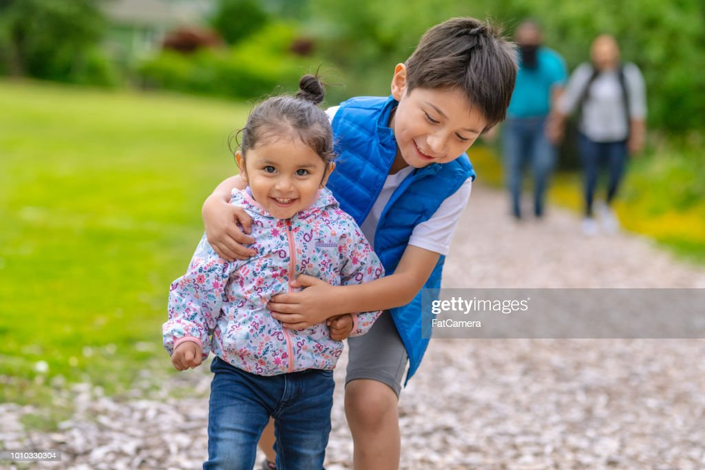 Two young kids and their parents walking out in nature : Stock Photo