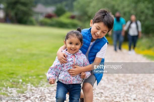 2人の若い子供とその両親が自然の中を歩いて出て行く - ネイティブアメリカン ストックフォトと画像