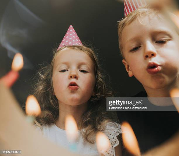 two young kids blowing out birthday candles - birthday stock pictures, royalty-free photos & images