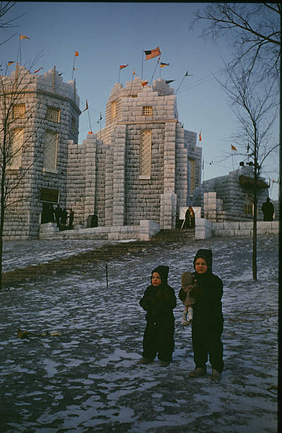 Two young kids play on the grounds in front of the Ice Palace made from blocks of ice during the StPaul Winter Carnival in StPaulMinnesota
