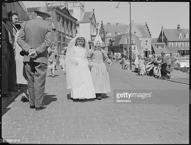 Two young ladies after their First Communion one in a traditional white dress the other in traditional Dutch clothing