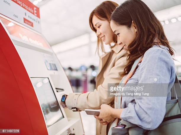 Two young ladies using check in kiosk at airport