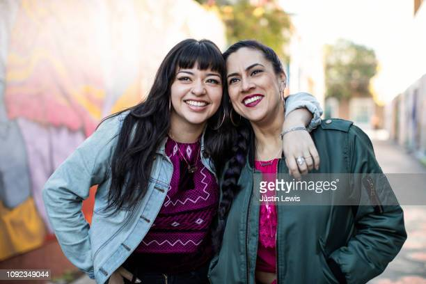 two young latina women leaning together, smiling and happy - bracelet photos stock pictures, royalty-free photos & images