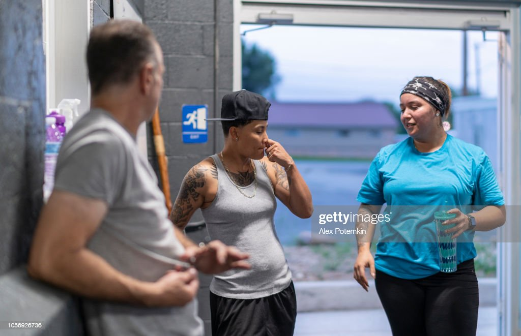 Two young Latino women talking with the coach, the senior man, in the gym after workout : Stock Photo