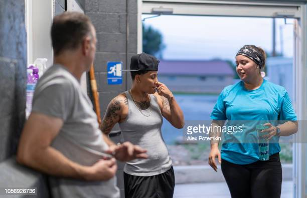 two young latino women talking with the coach, the senior man, in the gym after workout - alex potemkin or krakozawr latino fitness stock photos and pictures