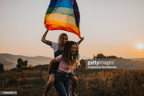 two young laughing happy woman couple hugging - happy flag day stock pictures, royalty-free photos & images