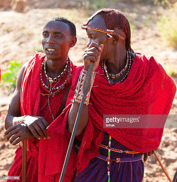 Two young maasai warriors with spear and traditional dress.